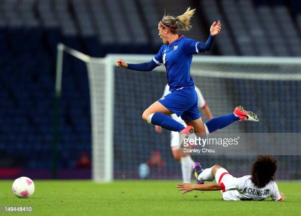 Camille Abily of France is tackled by Chung Sim of DPR Korea during the Women's Football first round Group G match between France and DPR Korea on...