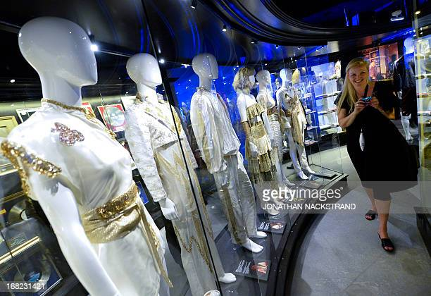 Camille BASWOHLERT A visitor pass by costumes of the members of Swedish disco band ABBA on May 7 2013 in Stockholm in the Gold Room at world's first...