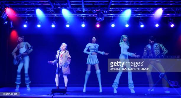 Camille BASWOHLERT A visitor sings as she enjoys a karaoke with giant holograms featuring members of Swedish disco band ABBA on May 7 2013 in...