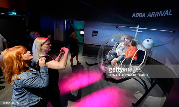 Camille BASWOHLERT Visitors pose for pictures in a chopper in which Swedish disco band ABBA members were photographed for a cover of their Arrival...