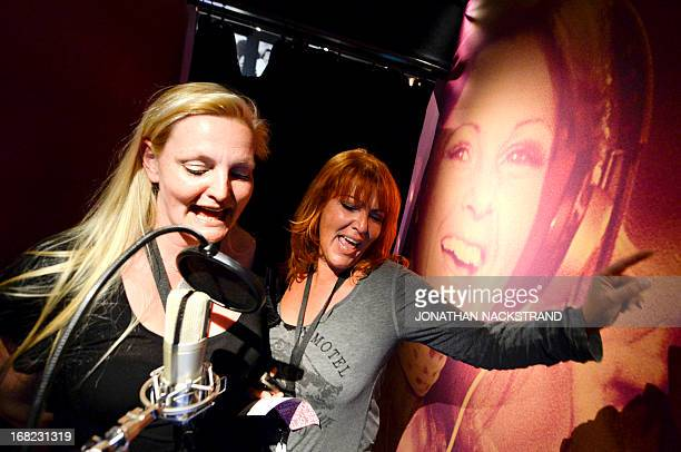 Camille BASWOHLERT Visitors sing in the recording room next to a giant photo displaying one member of Swedish disco band ABBA on May 7 2013 in...