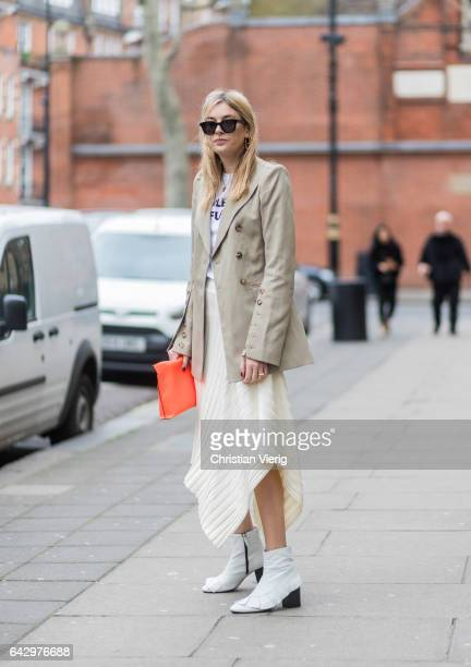 Camille Charriere wearing a beige jacket white skirt Loewe clutch outside Anya Hindmarch on day 3 of the London Fashion Week February 2017...