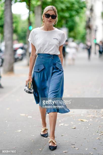Camille Charriere wears sunglasses a white tshirt a blue skirt a vichy gingham bag black shoes outside the Paul Smith show during Paris Fashion Week...