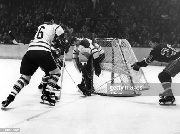 Camille Henry and Phil Goyette of the New York Rangers battle for the loose puck as goalie Johnny Bower of the Toronto Maple Leafs tries to cover as...