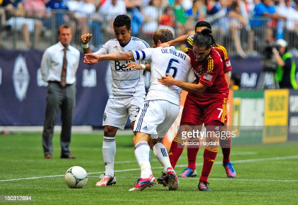 Camilo da Silva Sanvezzo of the Vancouver Whitecaps watches the ball while teammate Jay DeMerit gets grabbed by Fabian Espindola of Real Salt Lake...