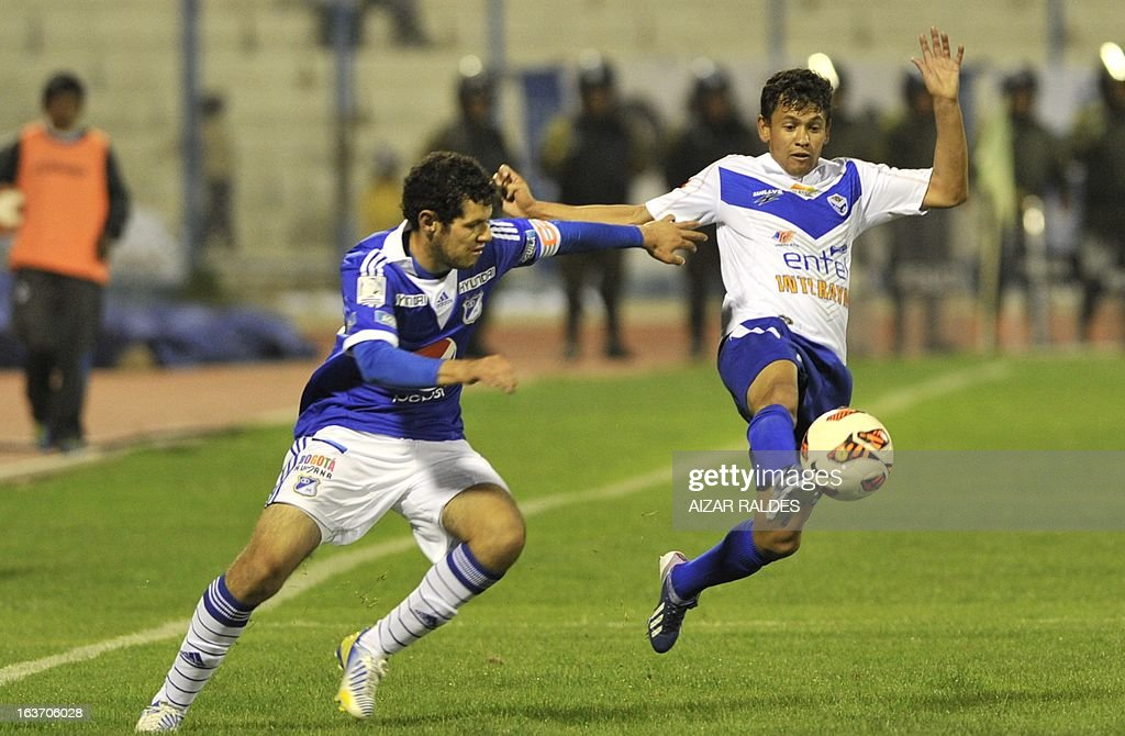 Camilo Franco (L) of Colombia´s Millonarios vies for the ball with Marcelo Gomez (R) of Bolivia's San Jose during their Copa Libertadores football match at Jesus Bermudez stadium in Oruro, Bolivia, on March 14, 2013.AFP PHOTO/Aizar Raldes