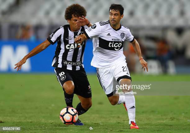 Camilo of Botafogo struggles for the ball with Julian Benitez of Olimpia during a match between Botafogo and Olimpia as part of Copa Bridgestone...