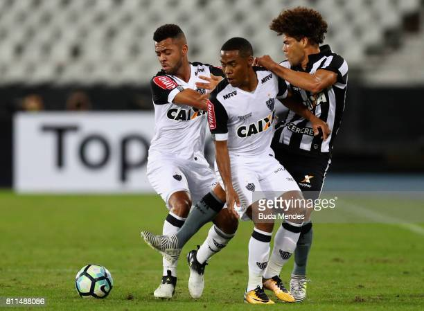 Camilo of Botafogo struggles for the ball with Rafael Carioca and Elias of Atletico MG during a match between Botafogo and Atletico MG as part of...