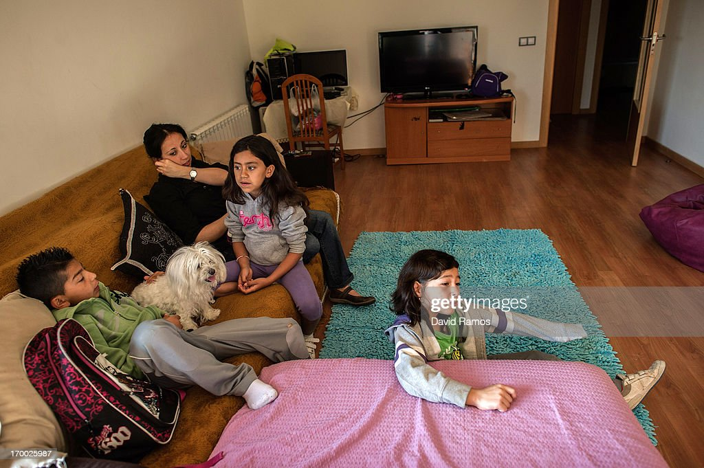 Camilo, 11, Pamela and her daugther Katalina,7, and Camilo's sister Inti, 9, sit on the sofa of Doris Perez's apartment in an occupied newly constructed building where she moved last March with her three grandchildren after being evicted a year ago after being unable to afford to pay a rent while living on her 350 Euro pension on June 5, 2013 in Salt, Spain. In 2010 Spanish banks foreclosed on more than 100,000 households contributing to the already large number of empty houses in Spain. With as many as one million properties unsold victims of Spain's financial crisis have turned to squatting in the empty buildings. This building has stood empty for two years before the anti-eviction platform of Girona and several homeless families moved in three months ago. The community houses a total of 8 families who have to suffer water and electricity cuts and live with the fear of eviction.