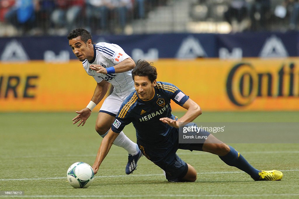 Camilo Sanvezzo #7 of the Vancouver Whitecaps chases the ball against <a gi-track='captionPersonalityLinkClicked' href=/galleries/search?phrase=Omar+Gonzalez&family=editorial&specificpeople=2488485 ng-click='$event.stopPropagation()'>Omar Gonzalez</a> #4 of the Los Angeles Galaxy during an MLS Game at B.C. Place on May 11, 2013 in Vancouver, British Columbia, Canada.