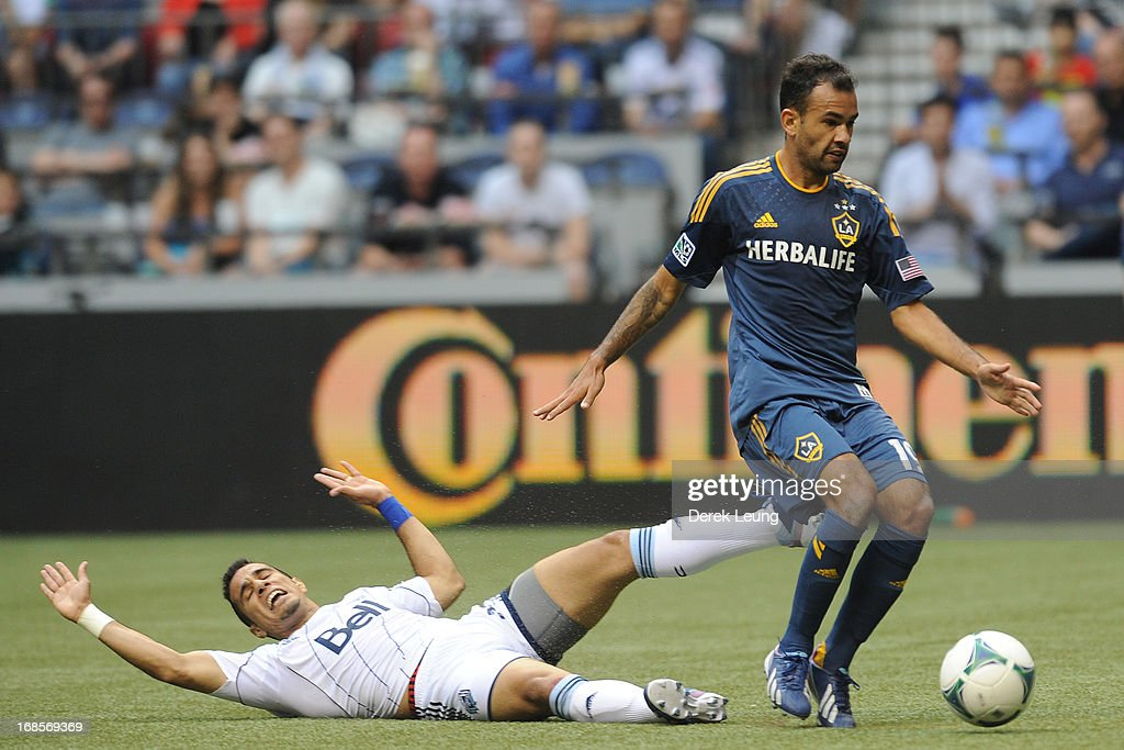 Camilo Sanvezzo #7 of the Vancouver Whitecaps gets checked by Juninho #19 of the Los Angeles Galaxy at B.C. Place on May 11, 2013 in Vancouver, British Columbia, Canada.
