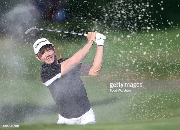 Camilo Villegas of Colombia plays a shot from the bunker on the 18th hole during the third round of the Wyndham Championship at Sedgefield Country...