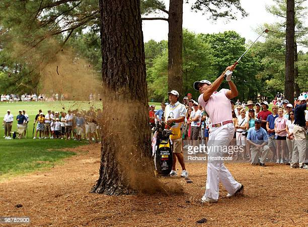 Camilo Villegas of Colombia plays from behind a tree trunk on the 5th during the third round of the Quail Hollow Championship at Quail Hollow Country...