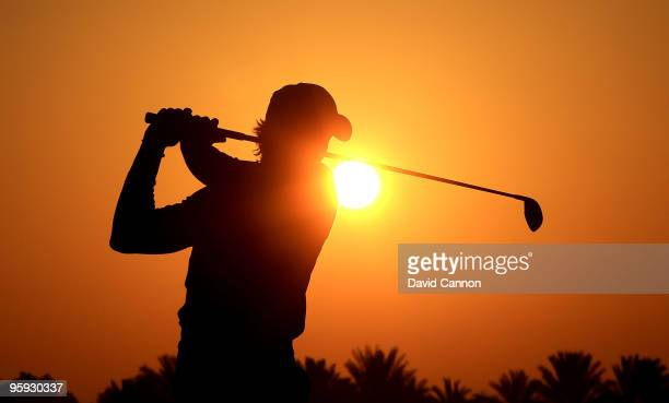 Camilo Villegas of Colombia warms up on the driving range against the rising desert sun before he started his second round of The Abu Dhabi Golf...