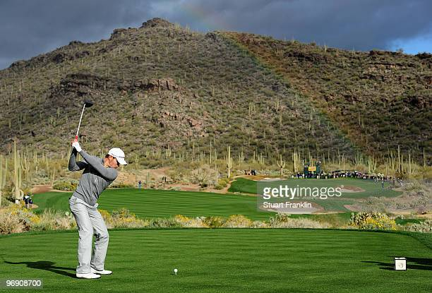 Camilo Villegas of Columbia plays his tee shot on the 15th hole as a rainbow appears during round four of the Accenture Match Play Championship at...