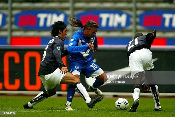 Camoranesi of Juventus and Roberto Baggio tussle for the ball during the Italian A 7th round match between Juventus and Brescia at delle alpi stadium...