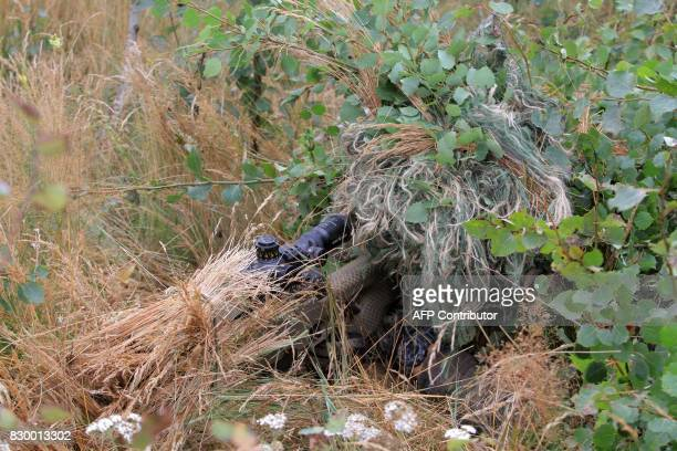 A camouflaged soldier serving in the NATO enhanced Forward Presence battalion battle group takes part in an exercise in Rukla Lithuania on August 11...