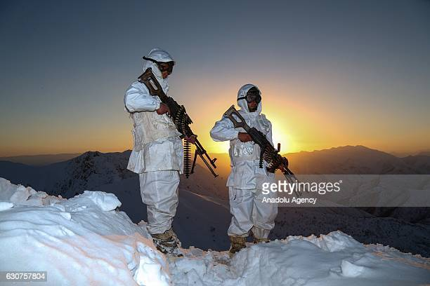Camouflaged Turkish soldiers keep watch on snow covered ground with their weapons during an operation against PKK terrorists as the sun sets in...