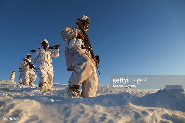 Camouflaged Turkish soldiers wade through snow with their weapons during an operation against PKK terrorists in Hakkari Turkey on December 30 2016...