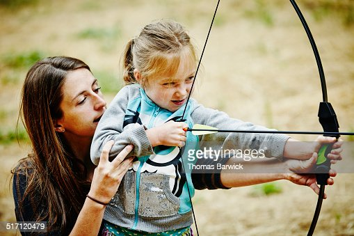 Camp counselor helping girl shoot bow and arrow