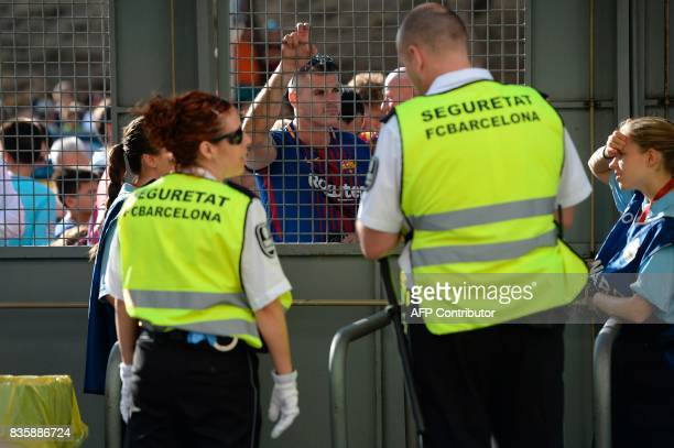 Camp Nou security members and football fans wait before the Spanish league footbal match FC Barcelona vs Real Betis at the Camp Nou stadium in...