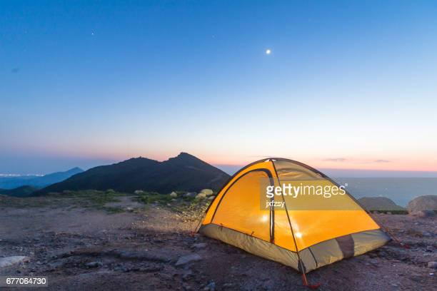 camp tent with light on under sky