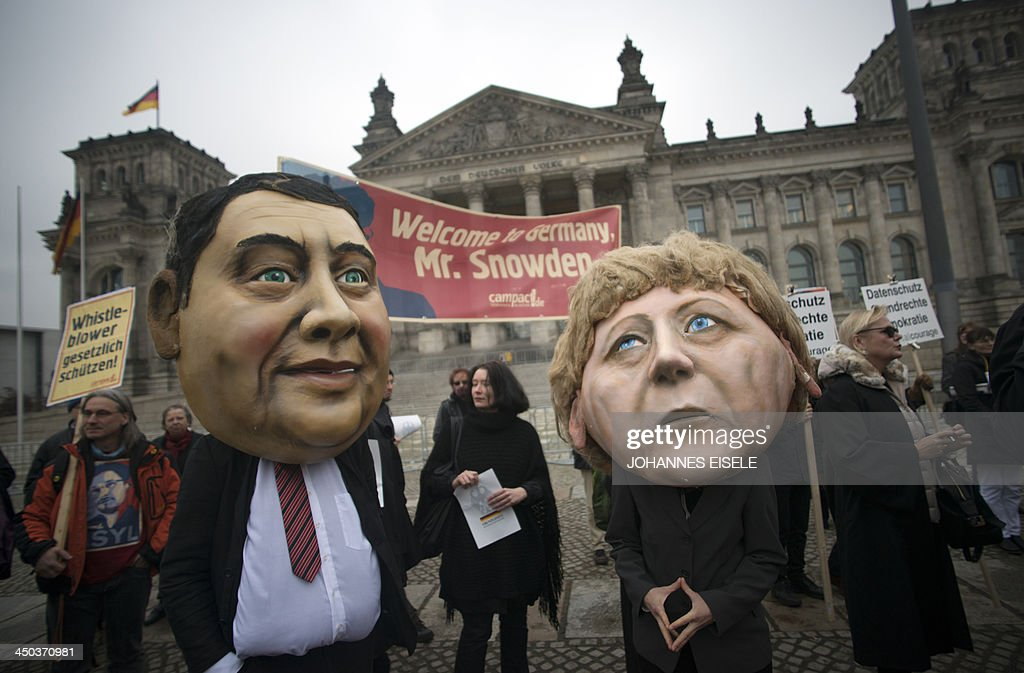 Campact activists wear masks of German Chancellor Angela Merkel (R) and the social democratic SPD party's leader Sigmar Gabriel and hold up a portrait of US whistleblower Edward Snowden in front of the Reichstag building housing the Bundestag (lower house of parliament) in Berlin on November 18, 2013. German MPs held a session at the Bundestag, focusing on the spying methods of the US National Security Agency (NSA) and its impact on Germany and transatlantic relationship. Snowden, former NSA contractor, had said before he was ready to help Germany following revelations, based on documents he provided, that have included the tapping of German Chancellor Angela Merkel's phone.