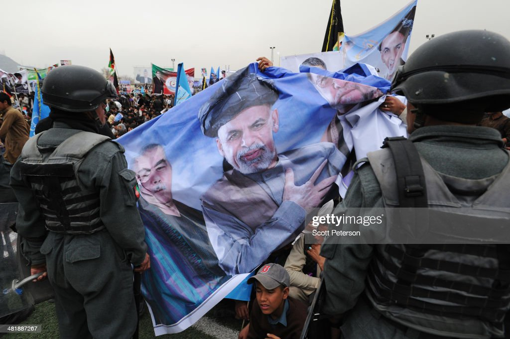 A campaign banner with Afghan Presidential Candidate Ashraf Ghani Ahmadzai passes besides police during a rally for thousands of supporters at the Ghazi stadium on April 1, 2014 in Kabul, Afghanistan. Mr. Ghani is a frontrunner in the April 5 vote to succeed President Hamid Karzai, in an election that is seen as a test of stability that will ensure continued Western donor aid for a nation torn by a Taliban insurgency. The Ghazi stadium is known as the site of amputations and executions during Taliban rule in the late 1990s.