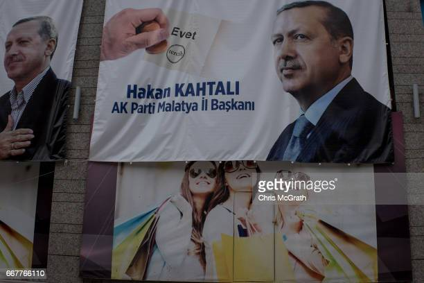 A 'EVET' campaign billboard showing the portrait of Turkish President Recep Tayyip Erdogan is seen over the top of a clothing advertisement at a...