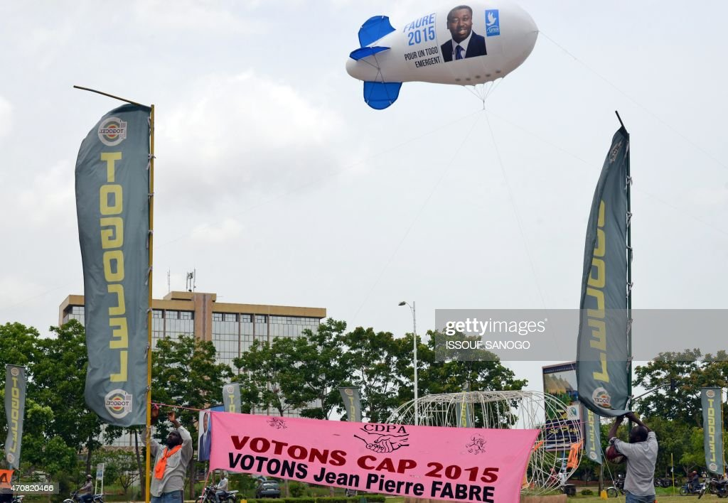 A campaign blimp with the portrait of President Faure Gnassingbe of Togo flies over workers hanging a sign for his opponent, UFC National Chairman <a gi-track='captionPersonalityLinkClicked' href=/galleries/search?phrase=Jean-Pierre+Fabre&family=editorial&specificpeople=2329955 ng-click='$event.stopPropagation()'>Jean-Pierre Fabre</a> in Lome on April 23, 2015. Gnassingbe is seeking his third term as President with elections beginning April 25, 2015. SANOGO