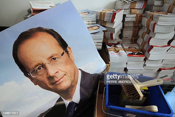 A campaign poster of France's opposition Socialist Party candidate for the 2012 presidential election Francois Hollande is set next to his program...