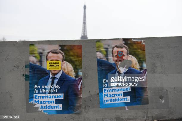 Campaign posters of French presidential election candidate for the En Marche movement Emmanuel Macron is seen in front of the Eiffel tower in Paris /...
