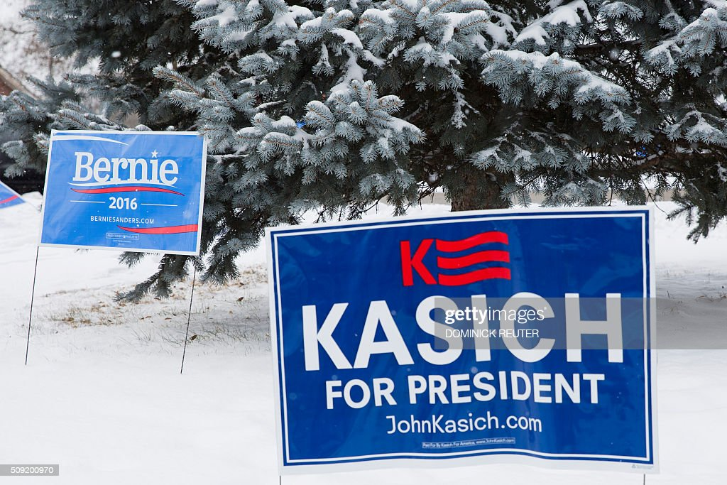 Campaign signs are seen in the snow outside a polling location, February 9, 2016, in Concord, New Hampshire. Voters head to the polls for the hundredth year as the first in the nation primary election. New Hampshire voters headed to polls at the snowy break of day Tuesday for the crucial first US presidential primary, with Donald Trump chasing victory and Hillary Clinton looking to narrow the gap on Bernie Sanders. / AFP / DOMINICK REUTER