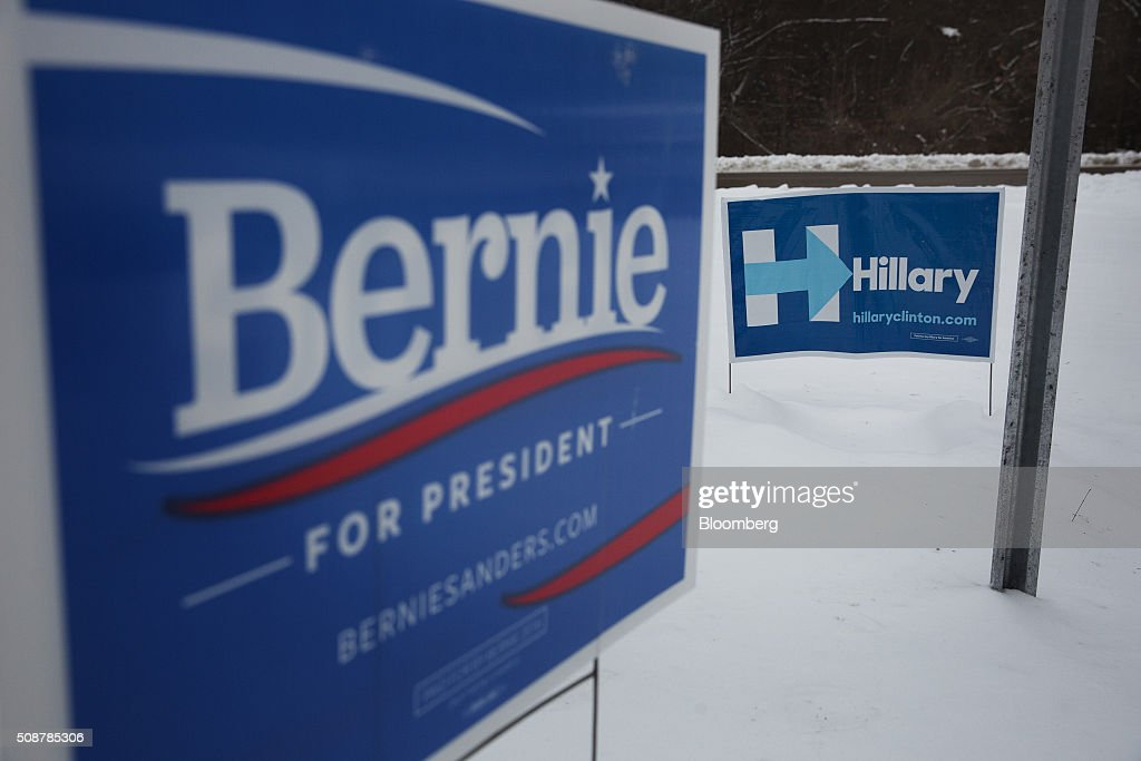 Campaign signs for 2016 Democratic presidential candidates Senator Bernie Sanders, an independent from Vermont, and Hillary Clinton, former Secretary of State, sit at a cross roads in Canterbury, New Hampshire, U.S., on Saturday, Feb. 6, 2016. On Tuesday, voters in New Hampshire will cast their ballots in the nation's first political primary of the election season. Photographer: Victor J. Blue/Bloomberg via Getty Images