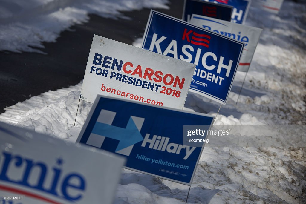 Campaign signs for 2016 presidential candidates former U.S. secretary of state Hillary Clinton, retired neurosurgeon Ben Carson, and John Kasich, governor of Ohio, are displayed outside a polling station at Broken Gound Elementary School in Concord, New Hampshire, U.S., on Tuesday, Feb. 9, 2016. Voters in New Hampshire took to the polls today in the nation's first primary in the U.S. presidential race. Photographer: Victor J. Blue/Bloomberg via Getty Images