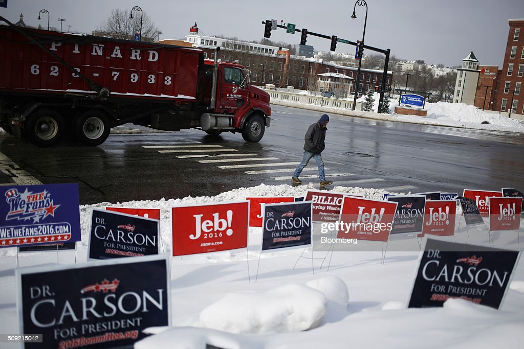 Campaign signs for 2016 Republican presidential candidates Jeb Bush, former governor of Florida, and Ben Carson, retired neurosurgeon, are displayed at an intersection in downtown Manchester, New Hampshire, U.S., on Tuesday, Feb. 9, 2016. Voters in New Hampshire took to the polls today in the nation's first primary in the U.S. presidential race. Photographer: Luke Sharrett/Bloomberg via Getty Images