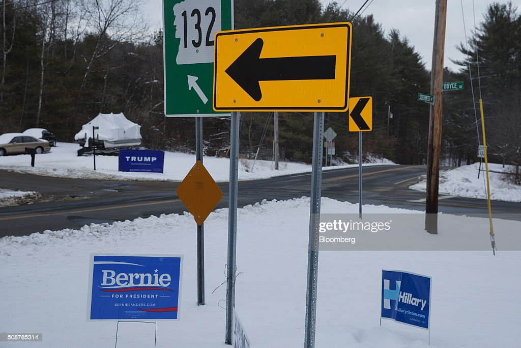 Campaign signs for Senator Bernie Sanders, an independent from Vermont and 2016 Democratic presidential candidate, Hillary Clinton, former Secretary of State and 2016 Democratic presidential candidate, and Donald Trump, president and chief executive of Trump Organization Inc. and 2016 Republican presidential candidate, sit at a cross roads in Canterbury, New Hampshire, U.S., on Saturday, Feb. 6, 2016. On Tuesday, voters in New Hampshire will cast their ballots in the nation's first political primary of the election season. Photographer: Victor J. Blue/Bloomberg via Getty Images
