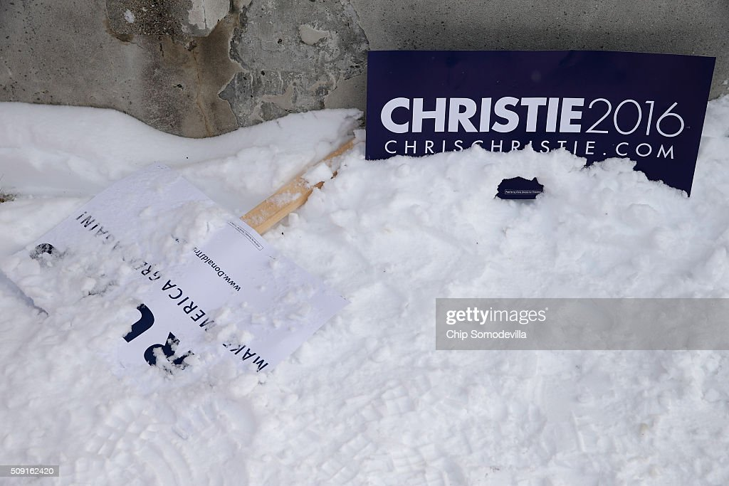 Campaign sings for Republican presidential candidates Donald Trump and New Jersey Governor Chris Christie lie on the ground outside the polling place at Webster School on primary day February 9, 2016 in Manchester, New Hampshire. Candidates from both parties are making last-minute attempts to swing voters to their side on the day of the 'First in the Nation' presidential primary.