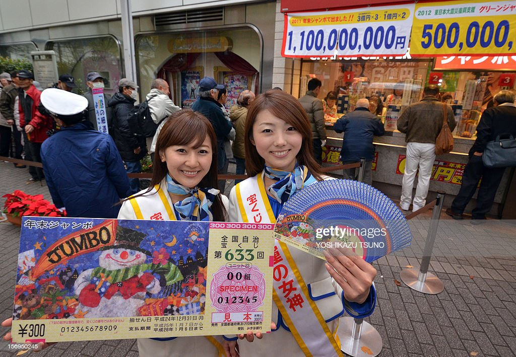 Campaign staff Mayuka Nakatani (L) and Kumiko Wakai display sample lottery tickets as people queue to purchase tickets for the 600 million yen (7.3 million USD) year-end Jumbo Lottery in Tokyo on November 26, 2012. Thousands of punters queued up for tickets in the hope of becoming a millionaire. AFP PHOTO / Yoshikazu TSUNO