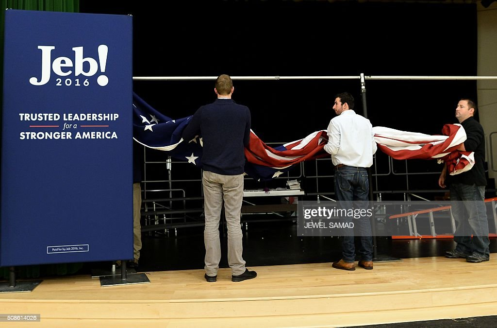 Campaign staff take off a US flag after US Republican presidential candidate Jeb Bush attended a Town Hall meeting in Concord, New Hampshire, on February 5, 2016. / AFP / JEWEL SAMAD