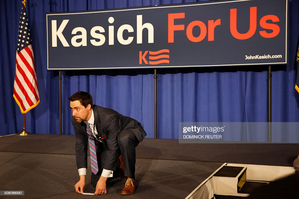 A campaign staffer places a stage marker as supporters of Ohio Governor and Republican presidential candidate John Kasich wait for results to come in during a primary election watch party, February 9, 2016, in Concord, New Hampshire. / AFP / DOMINICK REUTER