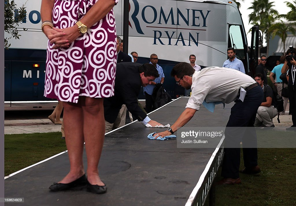 Campaign staffers for Republican presidential candidate, former Massachusetts Gov. Mitt Romney wipe down a runway as <a gi-track='captionPersonalityLinkClicked' href=/galleries/search?phrase=Ann+Romney&family=editorial&specificpeople=868004 ng-click='$event.stopPropagation()'>Ann Romney</a> (L) waits to walk on stage during a victory rally at Tradition Town Square on October 7, 2012 in Port St. Lucie, Florida. Mitt Romney is campaigning in Florida before traveling to Virginia where he is scheduled to give a foreign policy speech at the Virginia Military Institute.