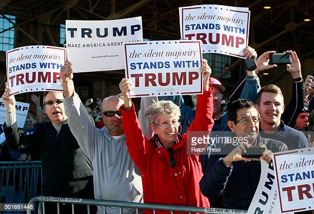 Campaign supporters hold up signs for Republican presidential candidate Donald Trump as his plane arrives to a campaign event at the International...