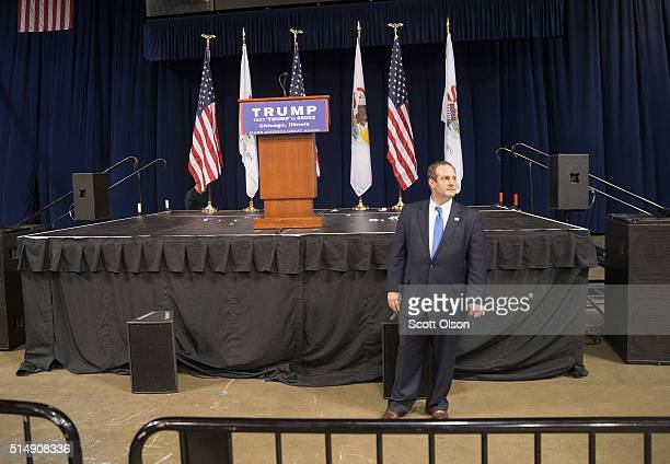 A campaign worker guards the podium after it was announced that a rally with Republican presidential candidate Donald Trump at the University of...
