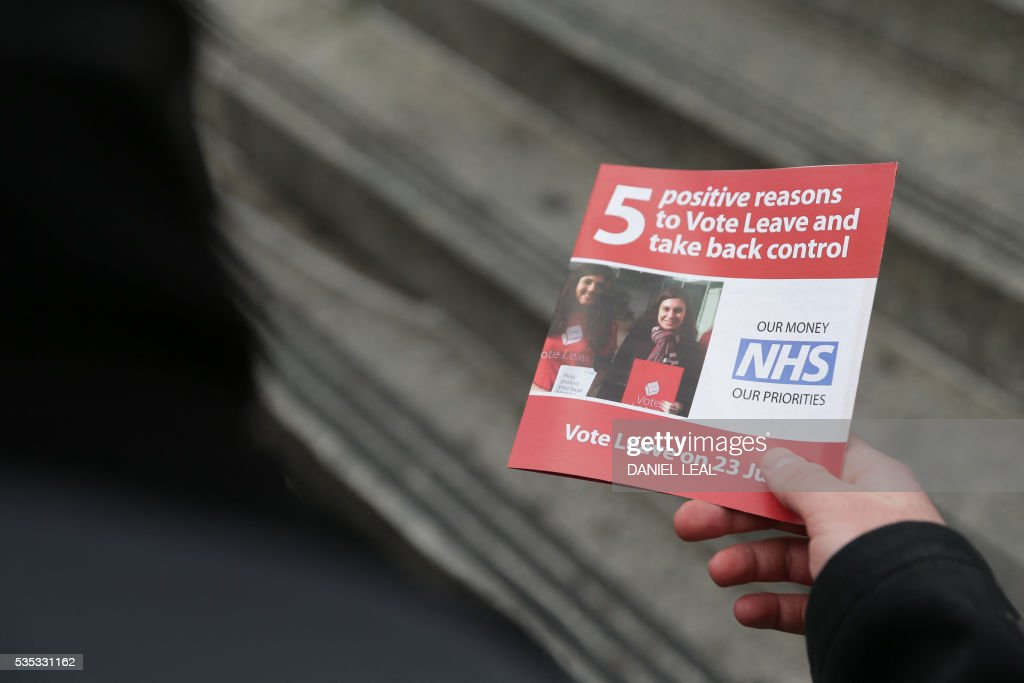 A campaigner for 'Vote Leave', the official 'Leave' campaign organisation for the forthcoming EU referendum, hands out leaflets outside Wembley Park tube station in north west London on May 29, 2016. Politicians and world leaders have dominated the headlines in the campaign for Britain's June 23 EU referendum, but a passionate battle for the country's future is also being fought by activists on the streets. / AFP / DANIEL