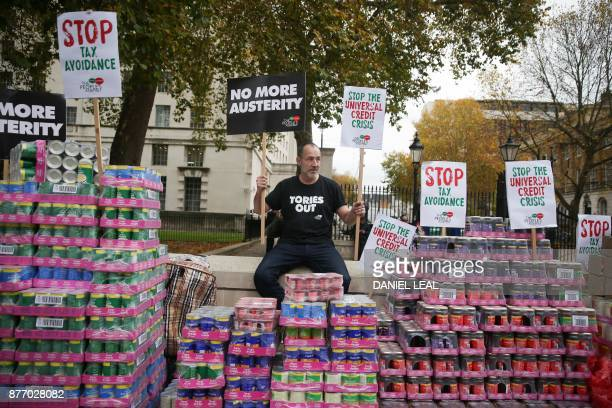 A campaigner protests against government austerity programmes next to crates of tinned food destined for food banks outside Downing street in central...