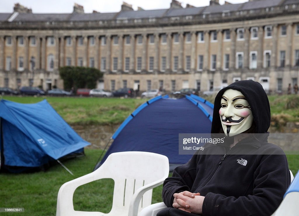 A campaigner, wearing an annonymous mask, from the Occupy Bath protest group sits in front of Bath's Grade 1 Royal Crescent on November 17, 2012 in Bath, England. The small group of local representatives of the Occupy movement - which staged an occupation in the city for six weeks last year - moved into Royal Victoria Park in front of the historic landmark on Friday night, but claimed they would end the protest on Sunday.