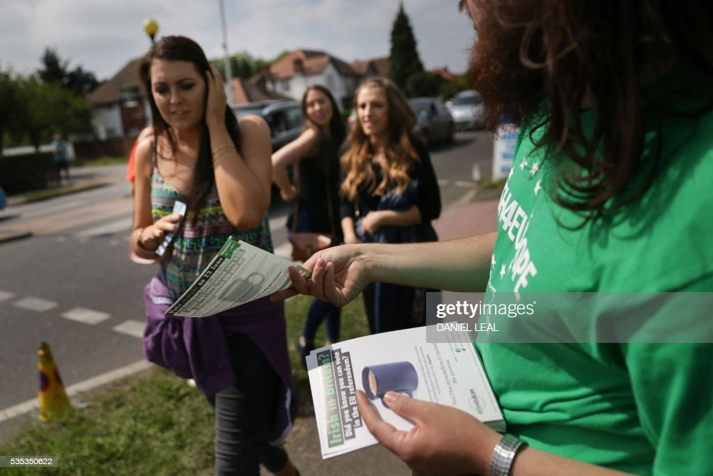 A campaigner with the pro-Europe campaign group called 'Irish4Europe', an Irish group supporting the 'Remain' campaign for the forthcoming EU referendum, hands out leaflets to visitors to the London vs Mayo Gaelic Athletic Association (GAA) football game at Ruislip GAA grounds in Ruislip, northwest London, on May 29, 2016. Irish4Europe is a civic campaign to secure Britains future in the European Union. Activists were leafletting to raise awareness that Irish citizens living in the UK can vote in the EU referendum on June 23, 2016. / AFP / DANIEL