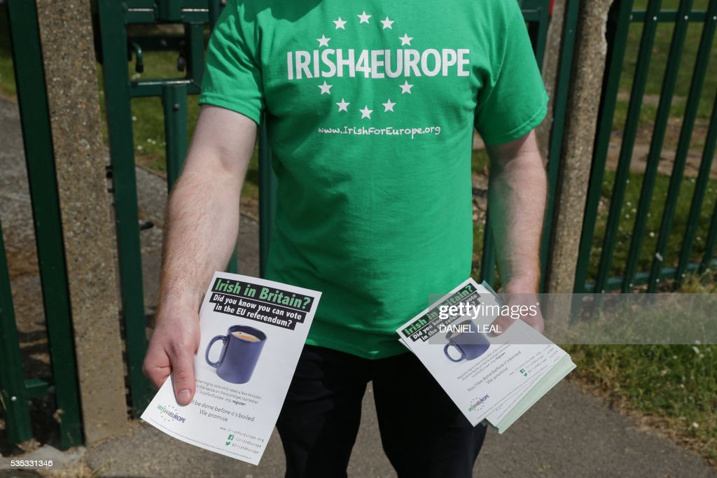 A campaigner with the pro-Europe campaign group called 'Irish4Europe', hands out leaflets to visitors to the London vs Mayo Gaelic Athletic Association (GAA) football game at Ruislip GAA grounds in Ruislip, northwest London, on May 29, 2016. Irish4Europe is a civic campaign to secure Britains future in the European Union. Activists were leafletting to raise awareness that Irish citizens living in the UK can vote in the EU referendum on June 23, 2016. / AFP / DANIEL