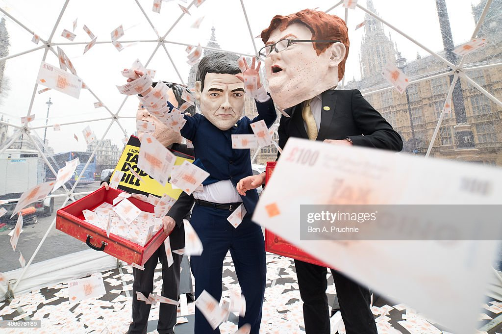 Campaigners dressed as the three chancellors, <a gi-track='captionPersonalityLinkClicked' href=/galleries/search?phrase=George+Osborne&family=editorial&specificpeople=5544226 ng-click='$event.stopPropagation()'>George Osborne</a>, <a gi-track='captionPersonalityLinkClicked' href=/galleries/search?phrase=Ed+Balls&family=editorial&specificpeople=3244683 ng-click='$event.stopPropagation()'>Ed Balls</a> and <a gi-track='captionPersonalityLinkClicked' href=/galleries/search?phrase=Danny+Alexander+-+Politician&family=editorial&specificpeople=6897330 ng-click='$event.stopPropagation()'>Danny Alexander</a>, wearing Oxfams famous big heads take part in a crystal dome cash grab stunt, on March 17, 2015 in London, England. The Tax Dodging Bill campaign is calling on all parties to pledge a series of measures to tackle corportate tax dodging and bring in billions of extra revenue to tackle poverty in the UK.